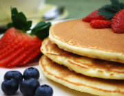 A stack of pancakes with blueberries and strawberries accenting the plate.