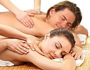 A couple (Female in foreground, Male in background) receiving a couples massage.